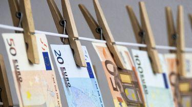 Een foto van een waslijn waar briefgeld aan hangt