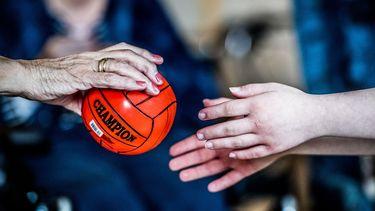 Iemand reikt een oudere vrouw een bal aan.