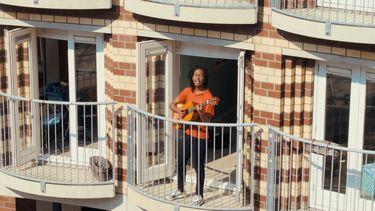 Jeangu Macrooy gitaarspelend op een balkon tijdens Woningsdag.