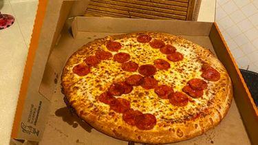 Op de foto een pizza met belegde pepperoni in de vorm van een hakenkruis.