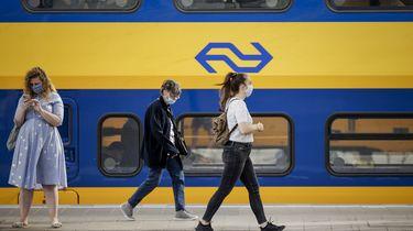 Op deze foto zijn treinreizigers te zien, met een mondkapje op. Ze lopen langs een NS-trein op het perron.