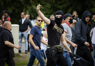 Een foto van een demonstrant die zijn middelvinger opsteekt tegen de politie.