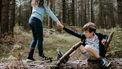 Op deze foto is een jong meisje te zien dat een leeftijdsgenootje omhoog helpt, nadat hij viel.