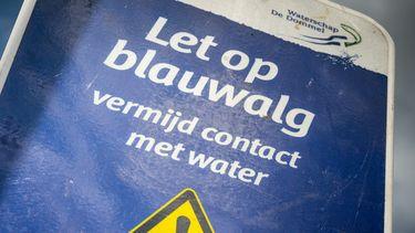 Een foto van een bord met een waarschuwing voor blauwalg