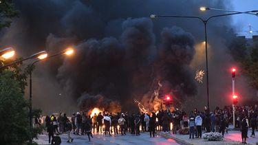 Op deze foto zijn de rellen in Malmo te zien, er hangt veel zwarte rook en er is vuur te zien.