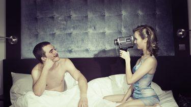 foto van filmend stel in bed