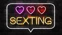 Op de foto zie je een neonreclamebord met het woord sexting en drie hartjes er boven.
