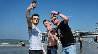 Een foto van jongens die op het strand van Scheveningen een selfie maken