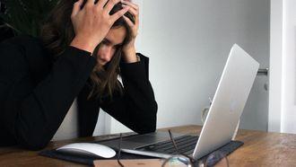 vrouw met hand in haar achter laptop