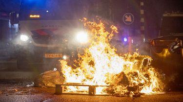 Op deze foto is een brand in de Schilderswijk in Den Haag te zien. Achter het vuur staat een auto van de politie.