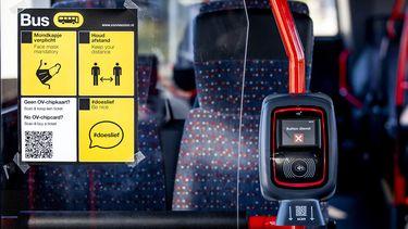 Op deze foto zie je een bordje in een bus met daarop de coronamaatregelen