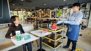 Op deze foto zie je een bezoeker in een fastfoodrestaurant. Bezoekers hoeven voortaan niet meer hun eigen dienblad op te ruimen.