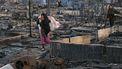 Een vrouw loopt door het verwoeste kamp.