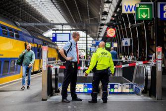 Een foto van een agent en een NS-medewerker op Amsterdam CS