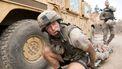 Een foto van een soldaat die knielt bij het wiel van een pantserwagen, hij sleept een gewonde medesoldaat op een brandcard mee