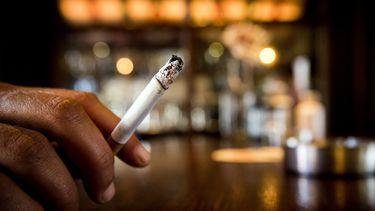 Een foto van een hand met een brandende sigaret. Zorgen Trimbos: meer twintigers zijn gaan roken.