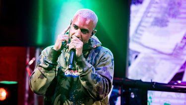Op deze foto is zanger en rapper Bizzey te zien op het podium, hij heeft een microfoon vast.