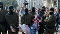 Op deze foto is te zien hoe een vrouw wordt weggedragen door vijf agenten.