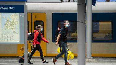 Een foto van reizigers op het perron die een mondkapje dragen