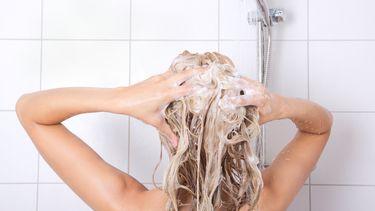 Een foto van een vrouw onder de douche, bezig met haar wassen