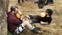 Op deze foto zie je twee mannen op een festival lachgas gebruiken.