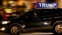 Een foto van een auto van een fan van Trump met een vlag