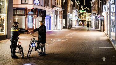 Een foto van een agent en een fietser tijdens de avondklok