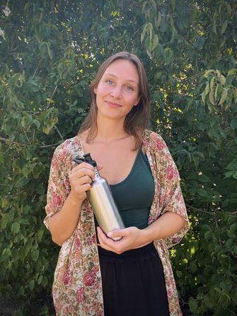 Een foto van Kiki Schollaardt met hergebruik-fles in de serie over zwerfafval