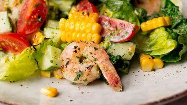 Op deze foto zie je maaltijdsalade met gegrilde sla, garnalen en maiskolven