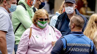 Op deze foto zijn meerdere mensen in Rotterdam te zien met een mondkapje op, ze praten met een boa.