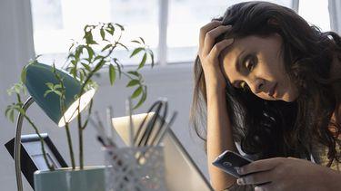 Op deze foto zie je een vrouw die veel werkstress heeft achter de laptop zetten.