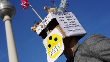 Een foto van een man met een gek masker die in Berlijn protesteert tegen de coronamaatregelen