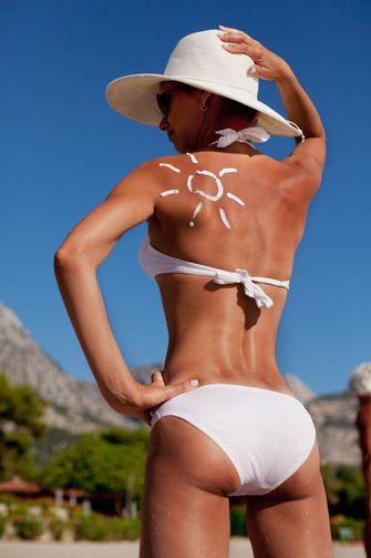 Een vrouw met op haar rug zonnebrandcreme in de vorm van een zonnetje.