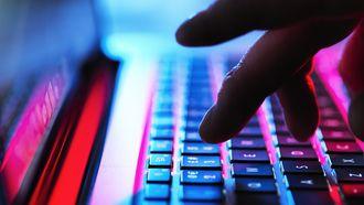 Op deze foto zie je een cybercrimineel bezig op een laptop. Vijf nep-bankmedewerkers opgepakt