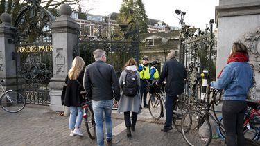 Een foto van mensen die het Vondelpark verlaten