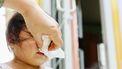 Een foto van een jong kind wiens neus wordt afgeveegd door een volwassene