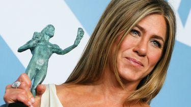 Een foto waarop actrice Jennifer Aniston te zien is met een prijs in haar hand.