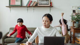 kinderen spelen terwijl moeder aan het thuiswerken is