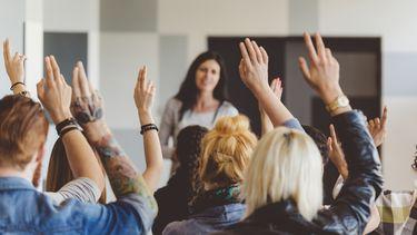 Een foto van een groep zittende mensen die hun hand opsteken, op de achtergrond hun leraar