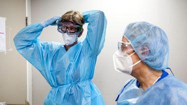 Een foto van twee zwaar ingepakte zorgmedewerkers die in aanmerking komen voor een zorgbonus