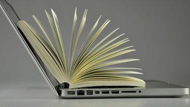 Op de foto een laptop met daarop een boek waarop de pagina's uiteen waaien