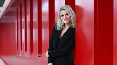 Een foto van Davina Michelle tegen een rode wand.