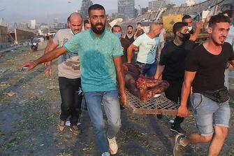Op deze foto zie je een slachtoffer van de explosie in Beiroet welke weggedragen wordt door diverse mannen op een brancard