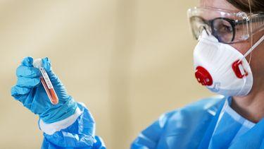 Een foto van een vrouw met een coronatest in haar hand