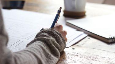 persoon schrijft op papier aan houten tafel