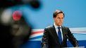 Een foto van een serieus kijkende premier Rutte tegen een blauwe achtergrond, een onscherpe filmcamera links in het beeld.