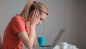 Een foto van een vrouw met geldproblemen achter haar laptop