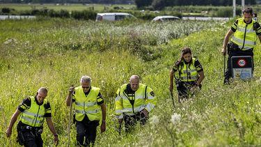 Op deze foto zie je politie doet die onderzoek doet in de berm op de plek waar Tamar van 14 jaar uit Marken is gevonden langs de dijk tussen Monnickendam en Marken. De politie is bezig met een zoektocht in de berm voor eventueel meer bewijs.