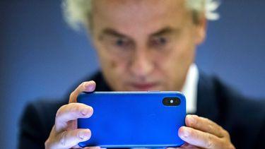 Op deze foto zie je Geert Wilders verschrikt op zijn mobiel kijken.