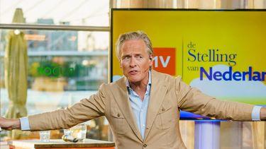 Een foto van Jort Kelder voor een scherm met de tekst 'de Stelling van Nederland'